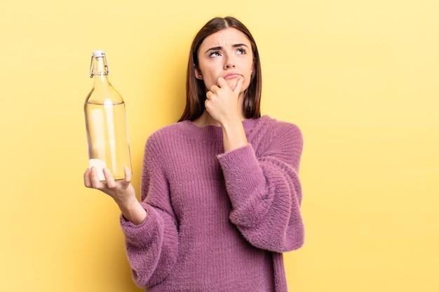 Jovem mulher hispânica pensando, sentindo-se duvidosa e confusa. conceito de garrafa de água