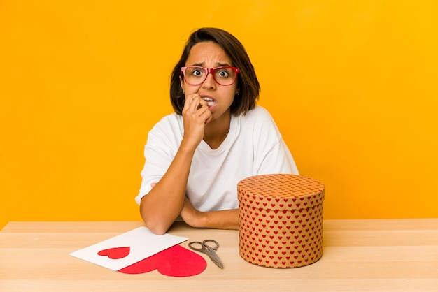 Jovem mulher hispânica preparando um presente de dia dos namorados isolada unhas roendo, nervosa e muito ansiosa.