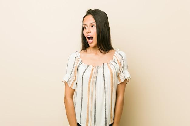 Jovem mulher hispânica que está chocada por causa de algo que viu.