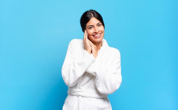 Jovem mulher hispânica se sentindo apaixonada e bonita, adorável e feliz, sorrindo romanticamente com as mãos ao lado do rosto. conceito de roupão de banho