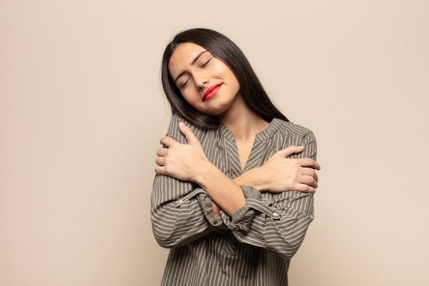 Jovem mulher hispânica se sentindo apaixonada, sorrindo, se acariciando e se abraçando, permanecendo solteira, sendo egoísta e egocêntrica