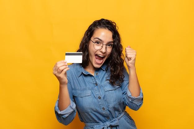 Jovem mulher hispânica se sentindo chocada, animada e feliz, rindo e comemorando o sucesso, dizendo uau!