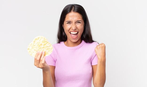 Jovem mulher hispânica se sentindo chocada, rindo e comemorando o sucesso e segurando um biscoito de arroz. conceito de dieta