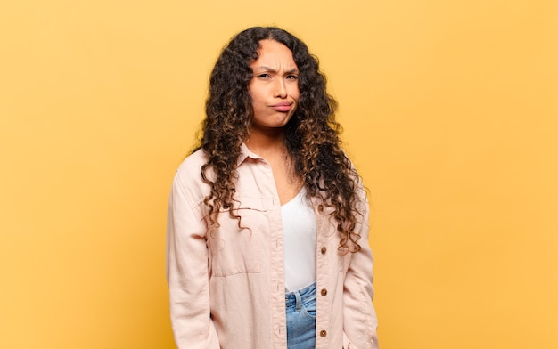 Jovem mulher hispânica se sentindo confusa e em dúvida, pensando ou tentando escolher ou tomar uma decisão