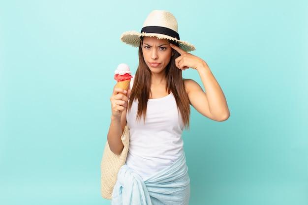 Jovem mulher hispânica se sentindo confusa e perplexa, mostrando que você está louca e segurando um sorvete. conceito de sumer