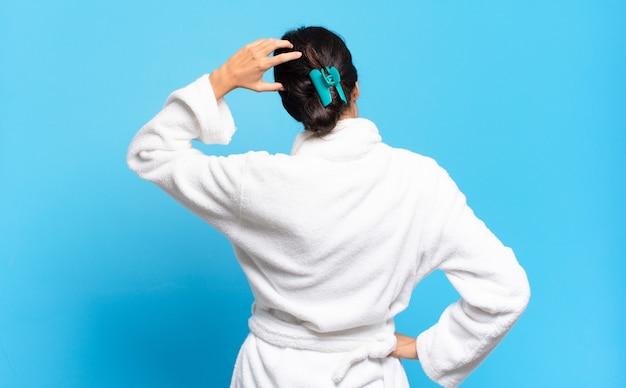 Jovem mulher hispânica se sentindo confusa e sem noção, pensando em uma solução, com a mão no quadril e a outra na cabeça, vista traseira. conceito de roupão de banho