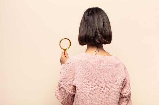Jovem mulher hispânica se sentindo confusa ou cheia ou dúvidas e perguntas, imaginando, com as mãos nos quadris, vista traseira
