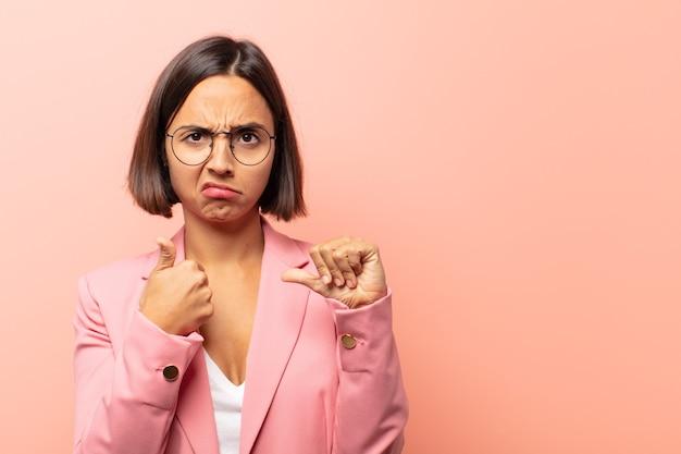 Jovem mulher hispânica se sentindo confusa, sem noção e insegura, avaliando o que há de bom e de ruim em diferentes opções ou escolhas