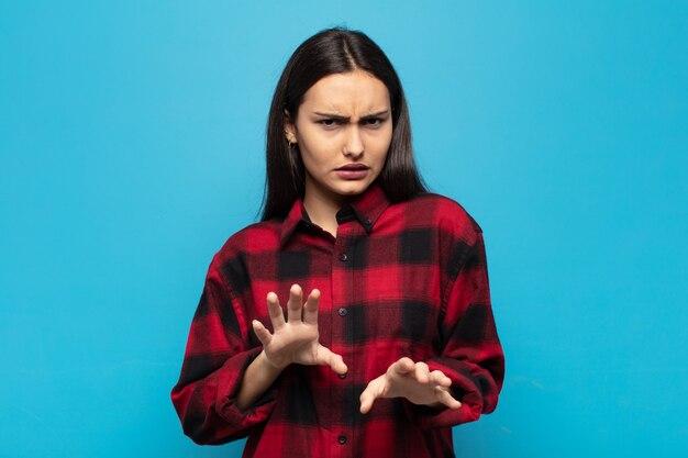 Jovem mulher hispânica se sentindo enojada e com náuseas, se afastando de algo desagradável, fedorento ou fedorento, dizendo eca