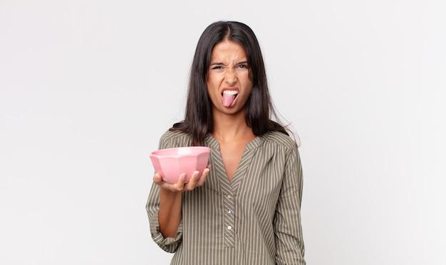 Jovem mulher hispânica se sentindo enojada e irritada, com a língua de fora e segurando uma tigela ou pote vazio