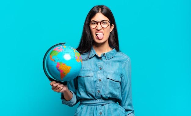 Jovem mulher hispânica se sentindo enojada e irritada, mostrando a língua, não gostando de algo nojento e nojento. conceito de planeta terra