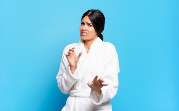 Jovem mulher hispânica se sentindo enojada e nauseada, se afastando de algo desagradável, fedorento ou fedorento, dizendo eca. conceito de roupão de banho
