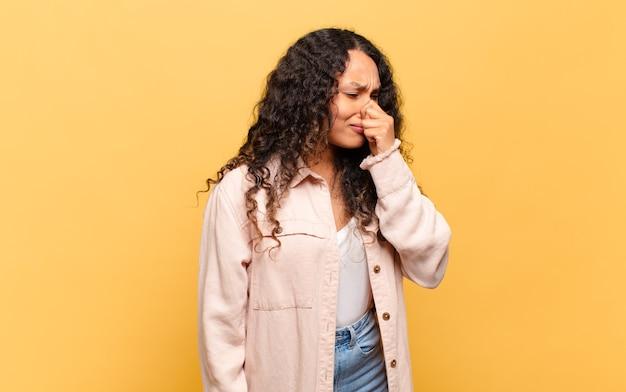 Jovem mulher hispânica se sentindo enojada, segurando o nariz para evitar cheirar um fedor desagradável