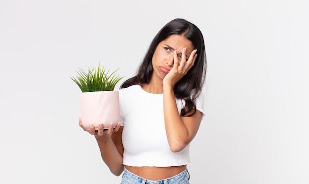 Jovem mulher hispânica se sentindo entediada, frustrada e com sono após uma sessão cansativa e segurando uma planta de casa decorativa