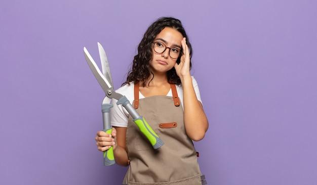 Jovem mulher hispânica se sentindo entediada, frustrada e com sono após uma tarefa cansativa, enfadonha e tediosa, segurando o rosto com a mão