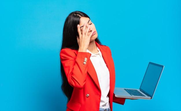 Jovem mulher hispânica se sentindo entediada, frustrada e com sono depois de uma tarefa cansativa, enfadonha e tediosa, segurando o rosto com a mão. conceito de laptop