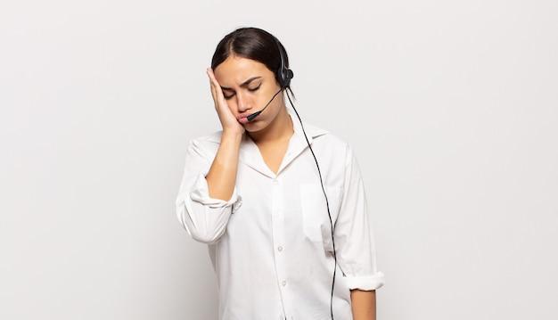 Jovem mulher hispânica se sentindo entediada, frustrada e com sono depois de uma tarefa cansativa, enfadonha e tediosa, segurando o rosto com a mão
