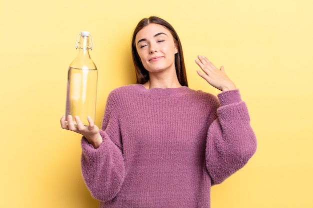 Jovem mulher hispânica se sentindo estressada, ansiosa, cansada e frustrada. conceito de garrafa de água