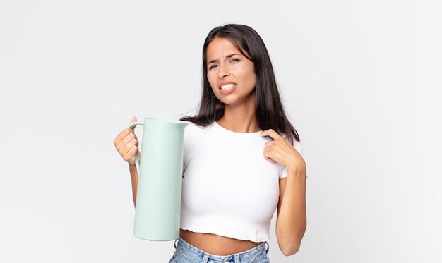 Jovem mulher hispânica se sentindo estressada, ansiosa, cansada e frustrada, segurando uma garrafa térmica de café