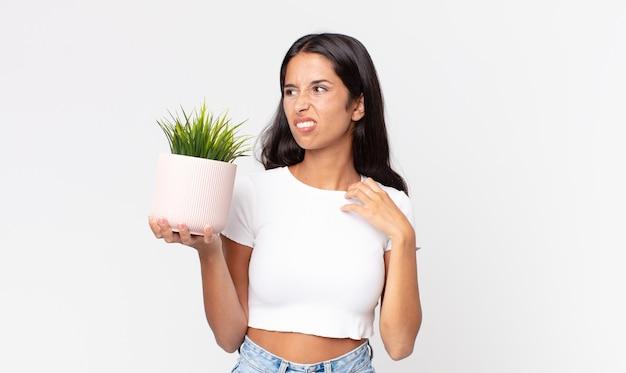 Jovem mulher hispânica se sentindo estressada, ansiosa, cansada e frustrada, segurando uma planta de casa decorativa