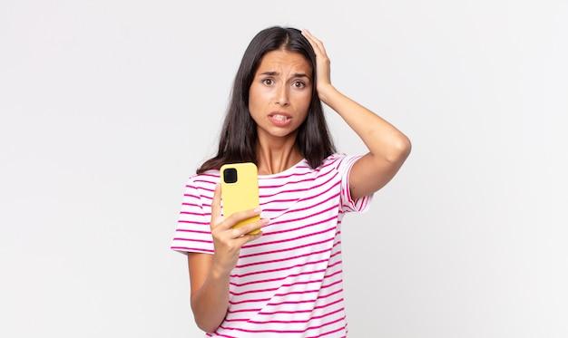 Jovem mulher hispânica se sentindo estressada, ansiosa ou assustada, com as mãos na cabeça e segurando um smartphone