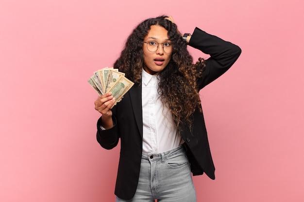 Jovem mulher hispânica se sentindo estressada, preocupada, ansiosa ou com medo, com as mãos na cabeça, entrando em pânico por engano. conceito de notas de dólar