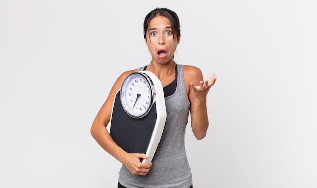 Jovem mulher hispânica se sentindo extremamente chocada e surpresa e segurando uma balança. conceito de dieta