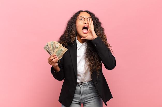 Jovem mulher hispânica se sentindo feliz, animada e positiva, dando um grande grito com as mãos perto da boca, gritando. conceito de notas de dólar