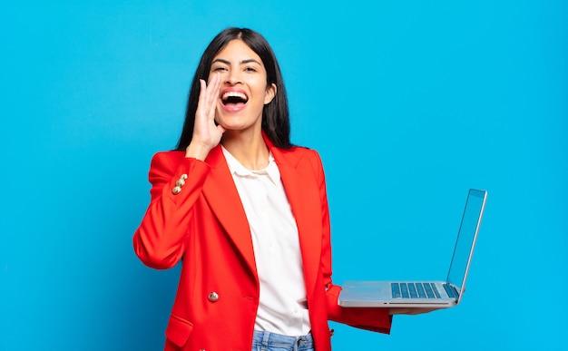 Jovem mulher hispânica se sentindo feliz, animada e positiva, dando um grande grito com as mãos perto da boca, gritando