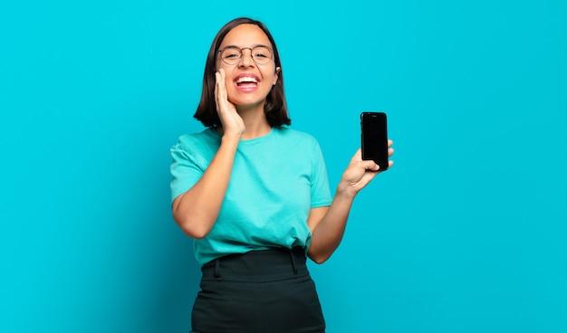 Jovem mulher hispânica se sentindo feliz, animada e positiva, dando um grande grito com as mãos perto da boca