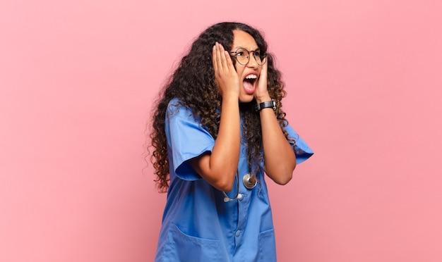 Jovem mulher hispânica se sentindo feliz, animada e surpresa, olhando para o lado com as duas mãos no rosto. conceito de enfermeira