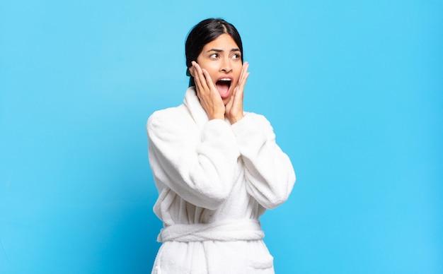 Jovem mulher hispânica se sentindo feliz, animada e surpresa, olhando para o lado com as duas mãos no rosto. conceito de roupão de banho