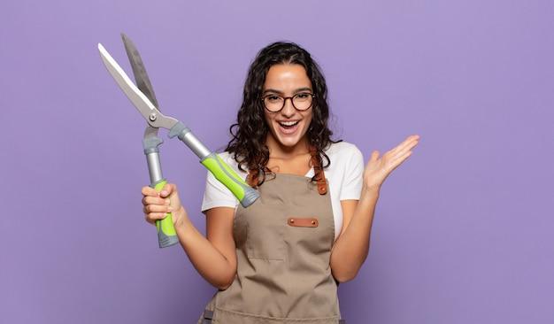 Jovem mulher hispânica se sentindo feliz, animada, surpresa ou chocada, sorrindo e atônita com algo inacreditável