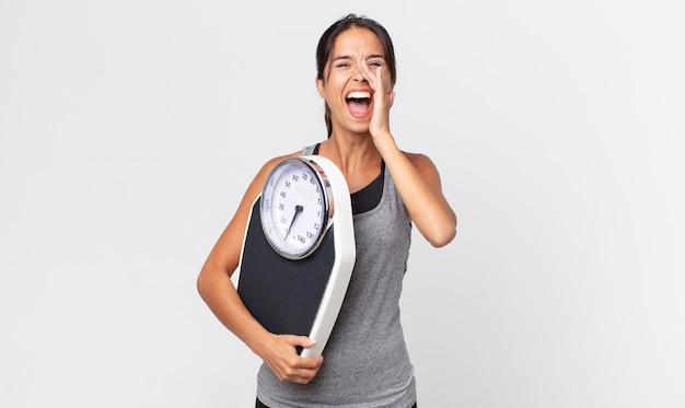 Jovem mulher hispânica se sentindo feliz, dando um grande grito com as mãos perto da boca e segurando uma balança. conceito de dieta