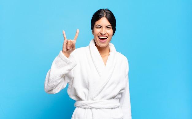 Jovem mulher hispânica se sentindo feliz, divertida, confiante, positiva e rebelde, fazendo sinal de rock ou heavy metal com a mão. conceito de roupão de banho