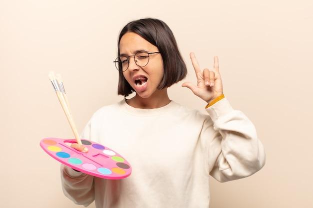Jovem mulher hispânica se sentindo feliz, divertida, confiante, positiva e rebelde, fazendo sinal de rock ou heavy metal com a mão