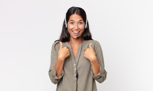 Jovem mulher hispânica se sentindo feliz e apontando para si mesma com um animado com um fone de ouvido. conceito de telemarketing