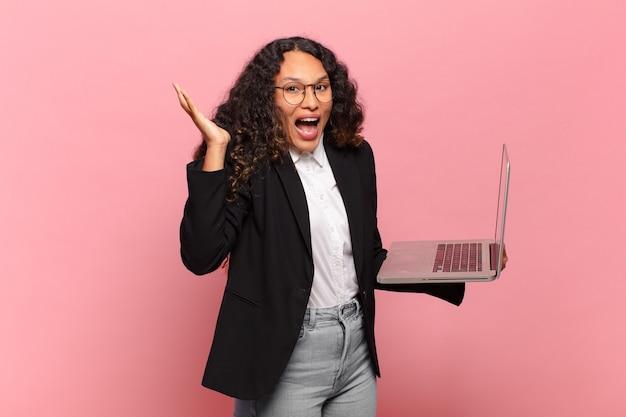Jovem mulher hispânica se sentindo feliz, excitada, surpresa ou chocada, sorrindo e atônita com algo inacreditável. conceito de laptop