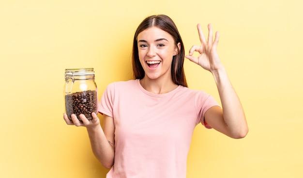 Jovem mulher hispânica se sentindo feliz, mostrando aprovação com um gesto certo. conceito de grãos de café