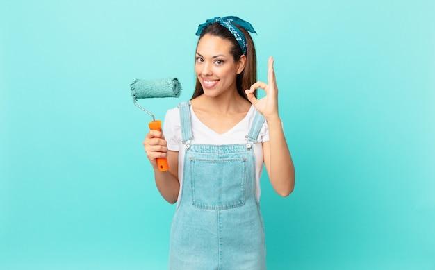 Jovem mulher hispânica se sentindo feliz, mostrando aprovação com um gesto de ok e pintando uma parede
