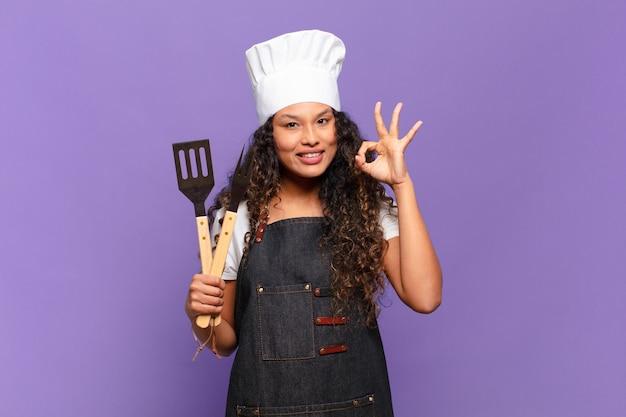 Jovem mulher hispânica se sentindo feliz, relaxada e satisfeita, mostrando aprovação com um gesto certo, sorrindo. conceito de chef de churrasco