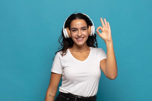 Jovem mulher hispânica se sentindo feliz, relaxada e satisfeita, mostrando aprovação com um gesto de ok, sorrindo