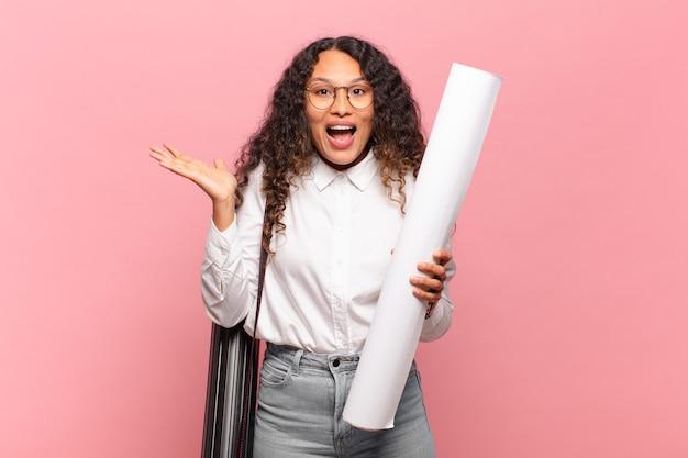 Jovem mulher hispânica se sentindo feliz, surpresa e alegre, sorrindo com atitude positiva, percebendo uma solução ou ideia