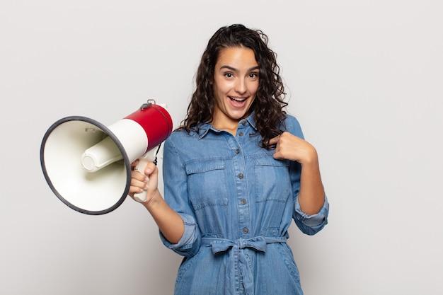 Jovem mulher hispânica se sentindo feliz, surpresa e orgulhosa, apontando para si mesma com um olhar animado e surpreso