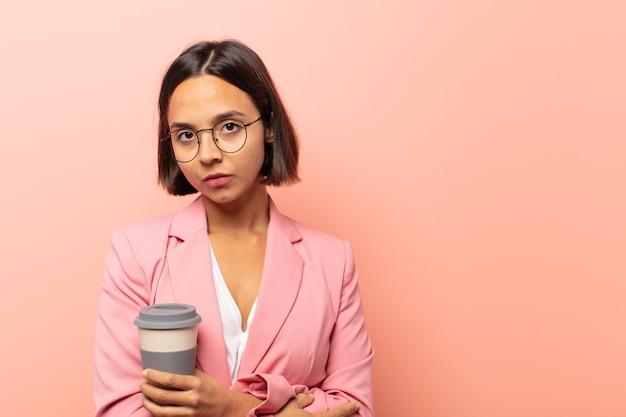 Jovem mulher hispânica se sentindo insatisfeita e desapontada, parecendo séria, irritada e com raiva de braços cruzados