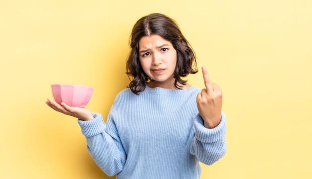 Jovem mulher hispânica se sentindo irritada, irritada, rebelde e agressiva. conceito de tigela vazia