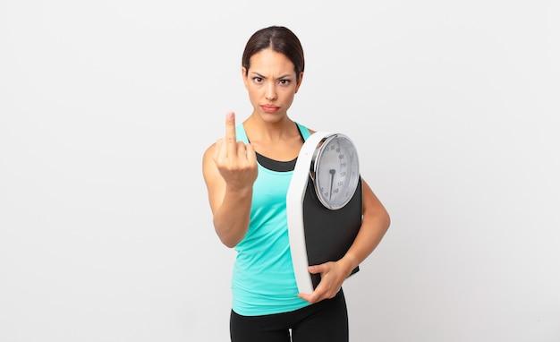 Jovem mulher hispânica se sentindo irritada, irritada, rebelde e agressiva e segurando uma balança