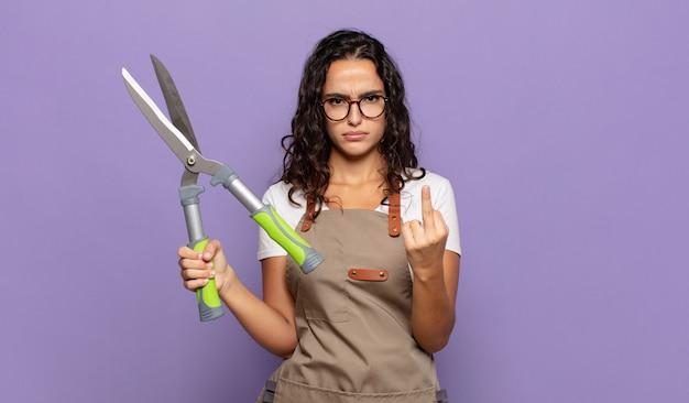 Jovem mulher hispânica se sentindo irritada, irritada, rebelde e agressiva, sacudindo o dedo do meio, lutando contra