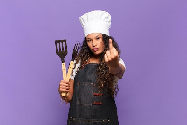 Jovem mulher hispânica se sentindo irritada, irritada, rebelde e agressiva, sacudindo o dedo médio, lutando de volta. conceito de chef de churrasco