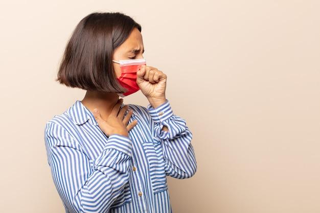 Jovem mulher hispânica se sentindo mal, com dor de garganta e sintomas de gripe, tosse com a boca coberta